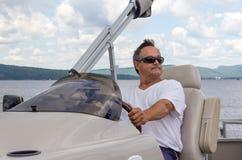 驾驶在湖的成熟人一条浮船小船 免版税库存照片