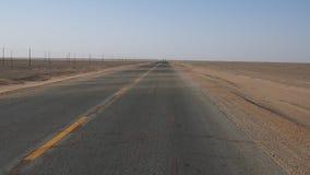 驾驶在空的沙漠路,沙子移动通过路由风,看起来的某人的观点一辆车波浪 股票视频
