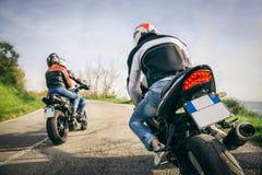 驾驶在自然的两辆摩托车 免版税库存照片