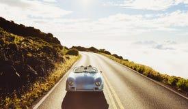 驾驶在葡萄酒跑车的乡下公路的小轿车 免版税图库摄影