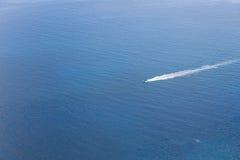 驾驶在蓝色海洋的一条小船的鸟瞰图 免版税图库摄影