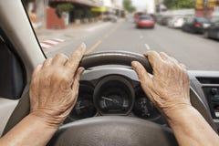 驾驶在街道上的资深妇女一辆汽车 库存照片