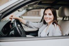 驾驶在街道的年轻美丽的微笑的女孩一辆汽车 免版税库存照片
