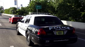 驾驶在街道迈阿密海滩警察美国都市风景的警车 股票录像