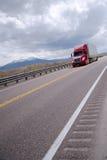 驾驶在被保护的高速公路的半红色卡车在内华达 库存照片