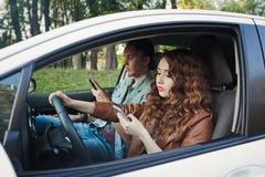 驾驶在路的一辆汽车和使用电话的女孩 免版税库存图片