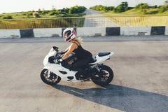 驾驶在路的妇女骑自行车的人一辆摩托车 库存照片