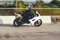 驾驶在路的妇女骑自行车的人一辆摩托车 图库摄影