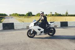 驾驶在路的妇女骑自行车的人一辆摩托车 免版税库存照片