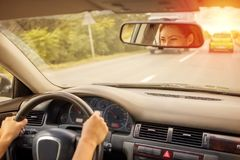 驾驶在路的美丽的妇女一辆汽车 库存图片