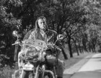 驾驶在路的骑自行车的人在森林里 免版税库存照片