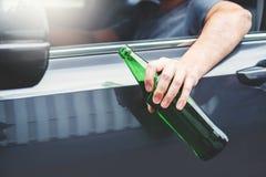 驾驶在路藏品瓶啤酒危险酒后驾车概念的醉酒的人一辆汽车 免版税图库摄影
