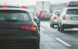驾驶在路高速公路的堵车汽车和卡车 图库摄影