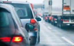驾驶在路高速公路的堵车汽车和卡车 库存图片