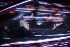 驾驶在车窗的夜,被阐明的和反射光的商人 免版税库存图片