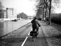 驾驶在运河附近的自行车道的骑自行车者 库存照片