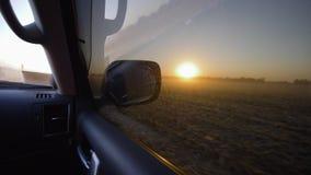 驾驶在通过一块干麦地的汽车,美好的风景在日落在秋天收获期间 影视素材