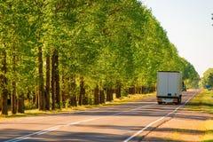 驾驶在郊区高速公路的货物卡车 免版税库存图片