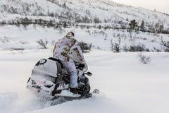 驾驶在雪的人雪上电车 库存照片