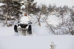 驾驶在雪的人雪上电车 免版税库存图片