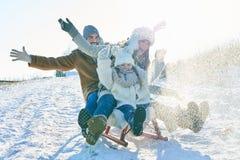驾驶在雪的家庭雪撬 库存图片