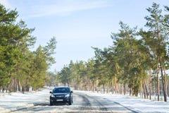 驾驶在雪道在冬天或早期的春天 从车窗的看法在有熔化的雪的路对此 免版税库存照片