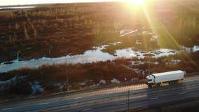 驾驶在高速公路入日落,正面图空中摄影机的一辆半卡车