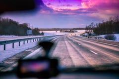 驾驶在高速公路在冬天在日落 免版税库存图片