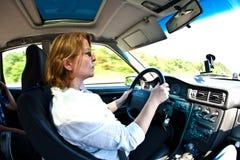 驾驶在高速公路的妇女汽车 库存照片