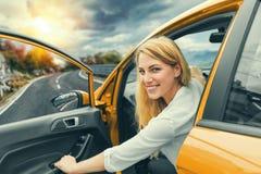 驾驶在高速公路的美丽的白肤金发的女孩一辆汽车 邀请旅行 出租汽车或假期 库存照片