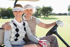 驾驶在他们多虫微笑的愉快的打高尔夫球的夫妇对照相机 免版税库存照片