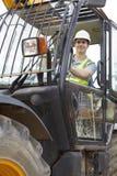 驾驶在建筑工地的建筑工人挖掘者 库存照片