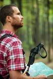 驾驶坚定的年轻人步行通过豪华的绿色森林,拿着地图和 免版税库存图片