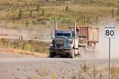 驾驶多灰尘的农村土路的工业用货车 免版税图库摄影