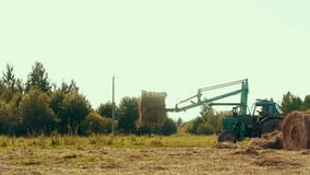 驾驶大包在农田的秸杆的农业拖拉机 农业机械 股票录像