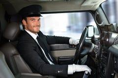 驾驶大型高级轿车微笑的英俊的汽车夫 免版税库存照片