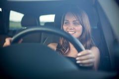 驾驶她新的汽车的逗人喜爱的少年 免版税库存照片