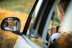 驾驶她的汽车的俏丽,少妇 免版税库存照片