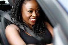 驾驶她的汽车的可爱的非洲妇女 免版税图库摄影
