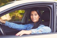 驾驶她的汽车的年轻美女 免版税库存图片