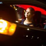 驾驶她的现代汽车的俏丽,少妇在晚上,在城市 免版税库存照片