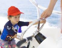 驾驶小船的愉快的男孩,享受夏天 免版税图库摄影