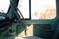 驾驶席和在一辆生锈的老绿色卡车方向盘 免版税库存照片