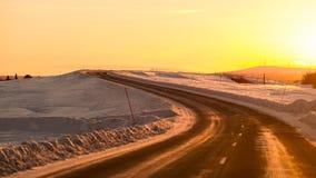 驾驶往在冬天路的太阳 库存图片