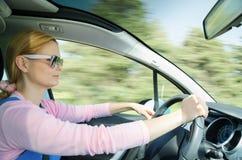 驾驶快速车的太阳镜的俏丽的妇女 免版税库存照片