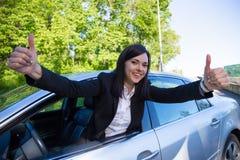 驾驶执照概念-有汽车的愉快的妇女 库存图片