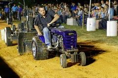驾驶拖拉机的人在拉扯竞争 免版税库存照片