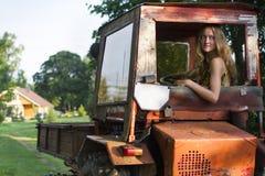 驾驶拖拉机的农夫女孩 免版税图库摄影