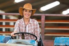 驾驶拖拉机的女性农夫 免版税库存图片