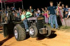 驾驶拖拉机的男孩在拉扯竞争 免版税库存图片